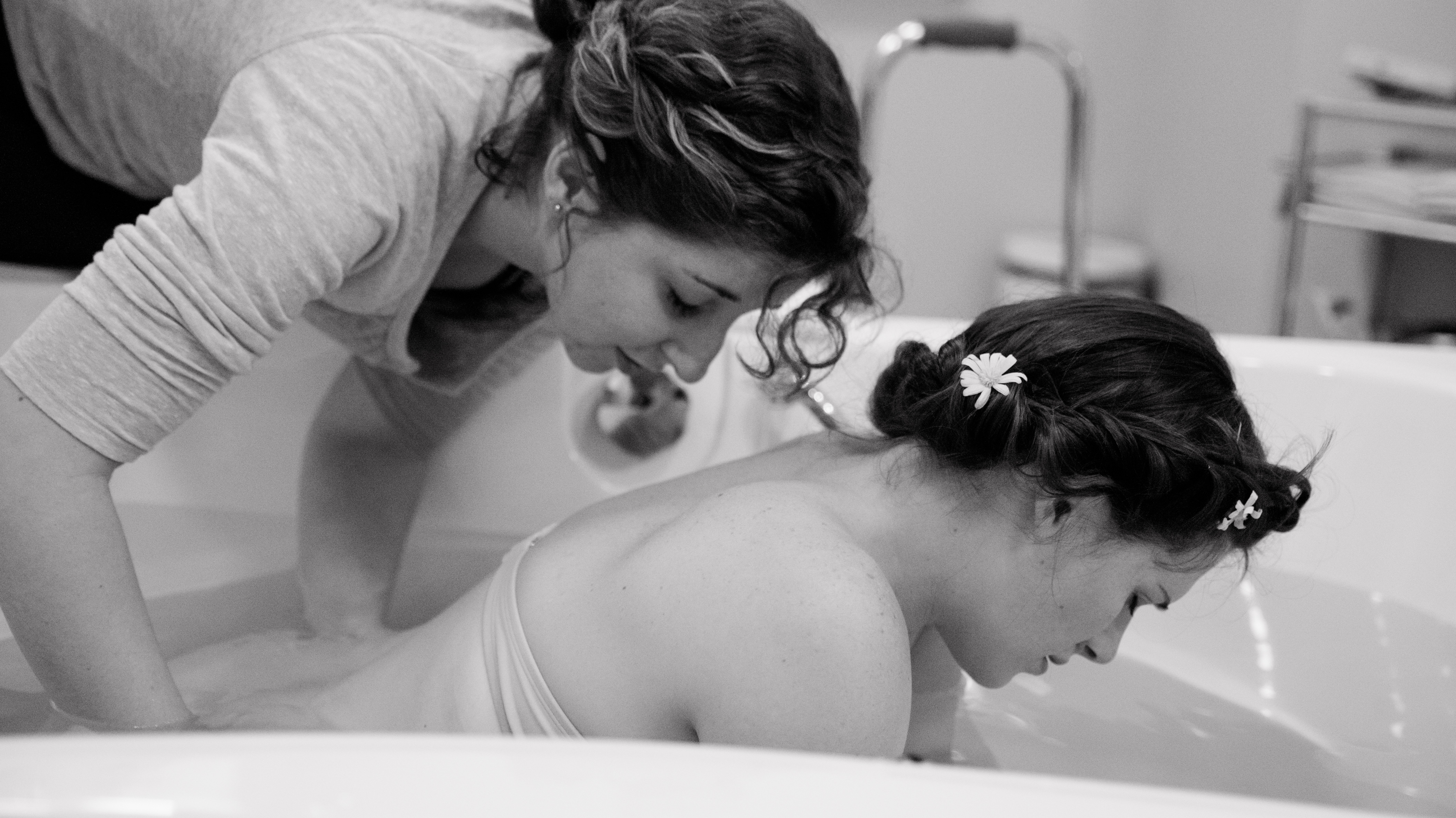 St. Pete doula applying counter-pressure to pregnant woman in tub.
