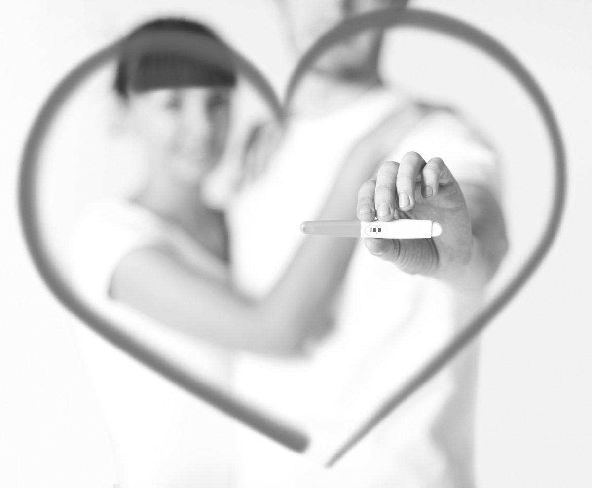 Couple holding positive pregnancy test surrounded by a heart