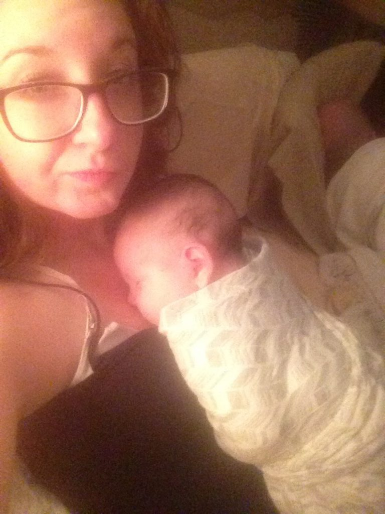 A mother scowling at the camera with a swaddled baby on her chest and her husband asleep in the background.